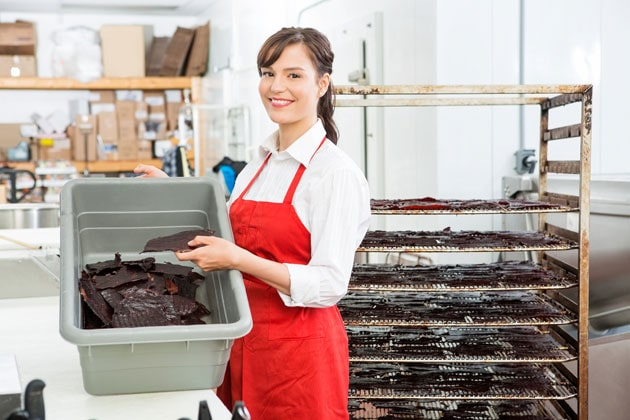 Beautiful woman with beef Jerky baking rack and container
